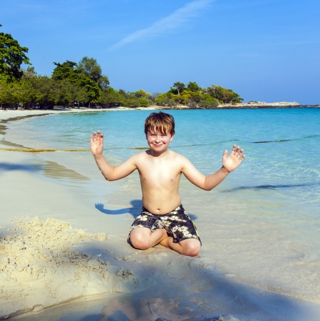 boy plays at the beautiful beach with sand and giving signs with his hands Stock Photo - 17250585
