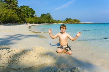 koh samet: boy plays at the beautiful beach with sand and giving signs with his hands Stock Photo
