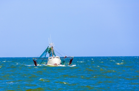 small fishing boat heading out to the ocean in late afternoon photo