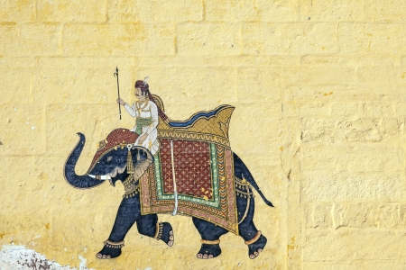 colorful indian mural in the fort at Jodhpur showing a royal procession, including elephant  from the Rajput era
