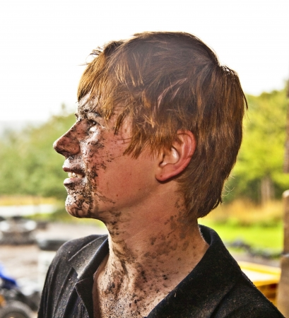 young boy is faszinated by quad driving and enjoyes is, his face is dirty from mud photo