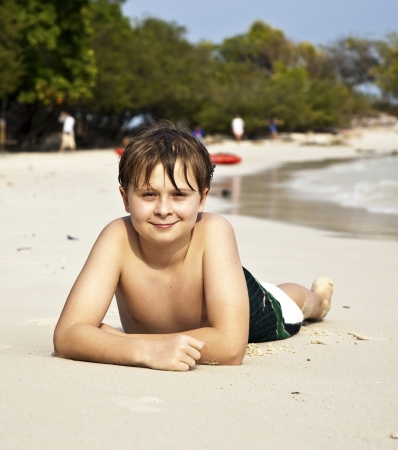 warmness: boy is lying at the beach and enjoying the warmness of the water and looking self confident and happy