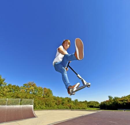 Junge springt mit seinem Roller