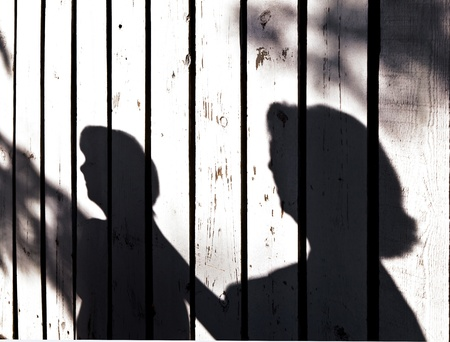 shadow of a boy with mother at a wooden fence photo