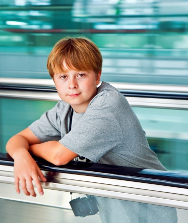 boy in the departure hall  in the new Airport Suvarnabhumi in Bangkok on a moving staircase photo