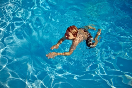backstroke: child enjoys swimming in the pool