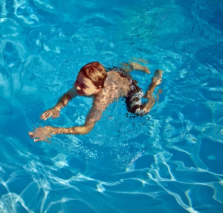 child enjoys swimming in the pool photo