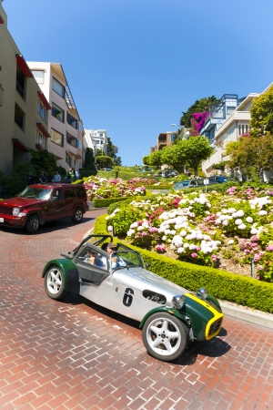 SAN FRANCISCO - JULY 23: Oldtimer passes the Lombard street on July 27, 2008 in San Francisco. It is  known for the  section on Russian Hill between Hyde and Leavenworth, in which the roadway has eight turns. Stock Photo - 17393192