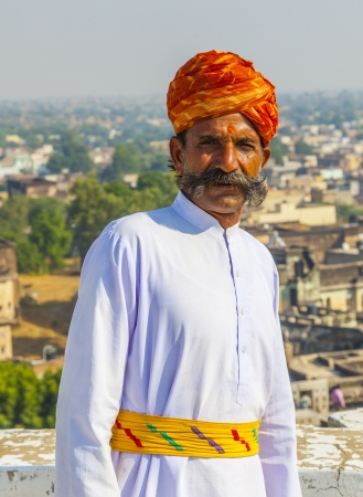 MANDAWA, INDIA - OCT 25: A Rajasthani man wearing traditional colorful turban and loves to pose in the palace for tourists on OCT 25, 2012 in Pushkar, Rajasthan, India. Hotels dress waiters in original clothes.