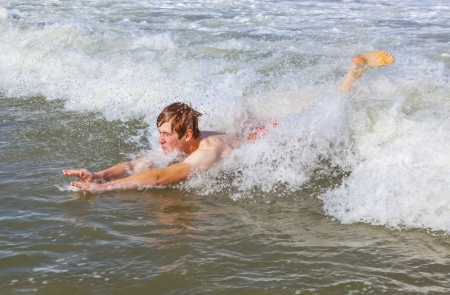 young boy is body surfing in the waves of the ocean photo