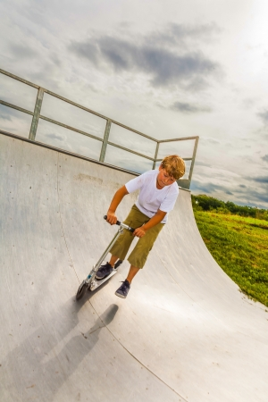 boy enjoys jumping with his scooter in the halfpipe photo