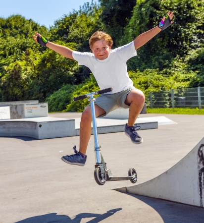 tenager: boy jumps with his scooter at the skate park Stock Photo