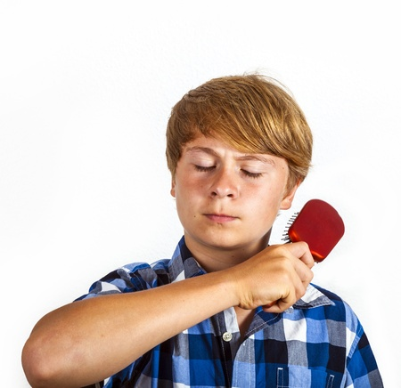 young boy brushing his hair photo