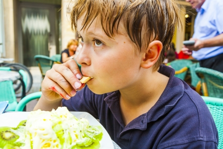 child is eating icecream at  a outdoor table photo