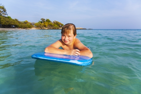 matress: boy is swimming on his surfboard and happily smiling in  a beautiful sea with crystal clear water and blue sky Stock Photo