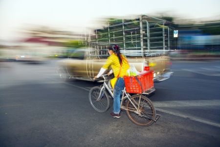 overtaking: BANGKOK - DEC 23:  lady drives home with bike from the market Pak Khlong Thalat on DEC 23,2009 in Bangkok, Thailand. The market was established by king Rama I 1782 and is the oldest flower market in Thailand. Editorial