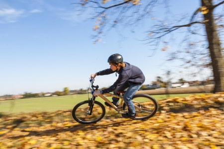 boy jumps with his dirt bike over natural ramps in open area and enjoys racing photo