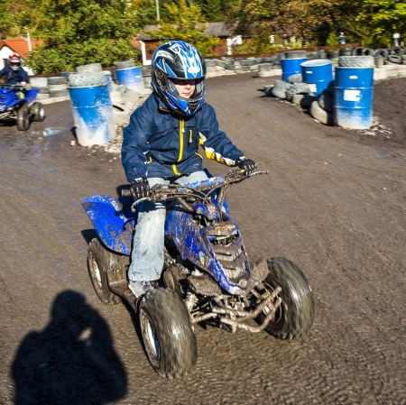 boy loves to race with a kart at the muddy kart track photo