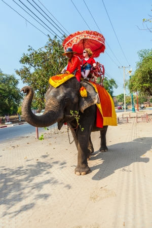 AYUTTHAYA, THAILAND DEC 23: tourists ride on an elephant in the Historical Park on DEC 23, 2009 in Ajutthaya, Thailand. It is called a must in Ayutthaya and costs about 1000 BATH for 30 min.