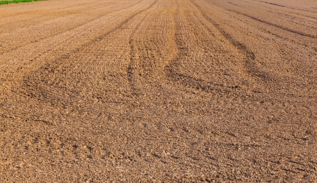 mark of tire on freshly plowed field photo