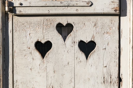 Heart shape look out on wooden door to outhouse. bleach photo