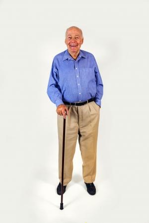 glücklich älterer Mann, der mit seinem Spazierstock isoliert auf weiß