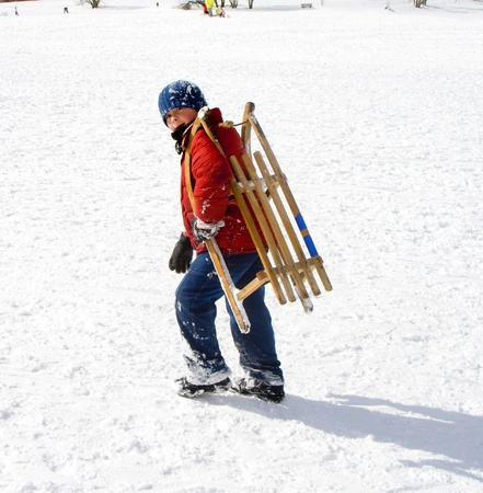 young boy in red jacket is sledding down the hill in winter photo