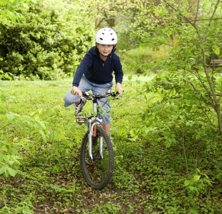 young boy with helmet is riding mountain bike photo