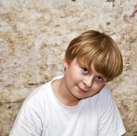 brown eyes: muchacho con el pelo castaño claro y ojos marrones lookes amable, feliz y sonríe, lleno de confianza en sí mismo positivo