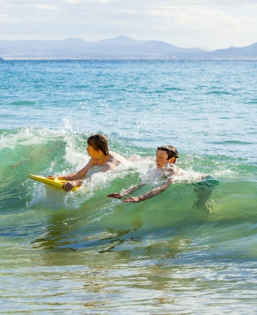 friendly competition: boys have fun riding in the waves