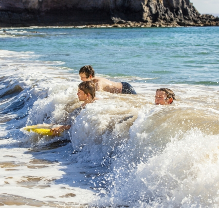 boys have fun riding in the waves photo