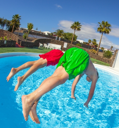boy has fun jumping in the pool photo