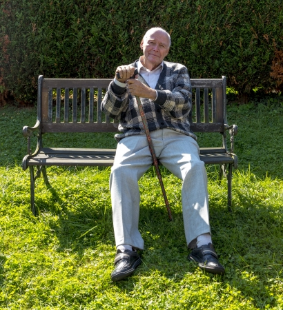 enjoys: old man enjoys sitting on a bench in his garden