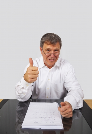 smart smiling business man shows thumbs up sign photo