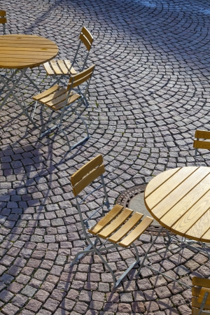Outdoor German cafe seating with round tables and wooden  chairs photo