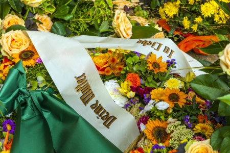 funeral background: flowers at the grave with sentence in love your mother Stock Photo