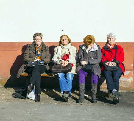 FRANKFURT, GERMANY- March 2: seniors enjoy first sunny day on a bench n Midday on March 2,2013 in Frankfurt, Germany. Until this day rankfurt had only 36 sun hours in 2013 which is a negative record. Stock Photo - 18329187