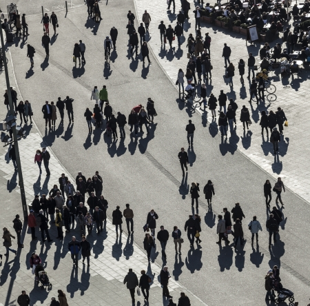 central square: people walk along the Zeil in Midday in Frankfurt with large shadows. The zeil is one of the most famous and busiest shopping streets in Germany.