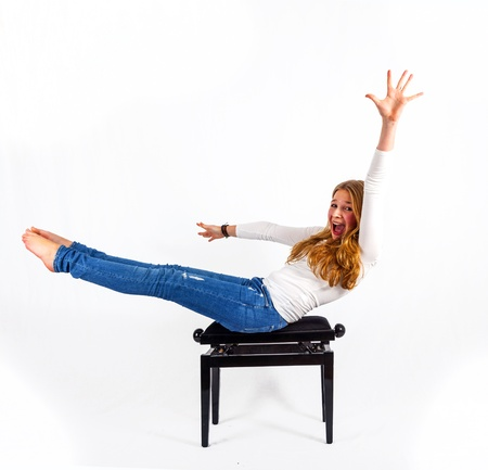 round chairs: attractive woman demonstrates fitness exercises on a piano chair Stock Photo