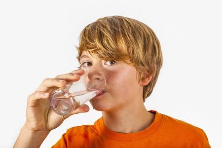 Netter Junge mit orangefarbenen T-Shirt Trinkwasser