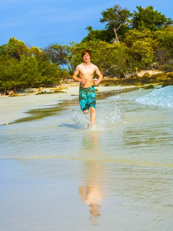 young boy with red hair in swimsuit is running along the beautiful beach and enjoys it photo
