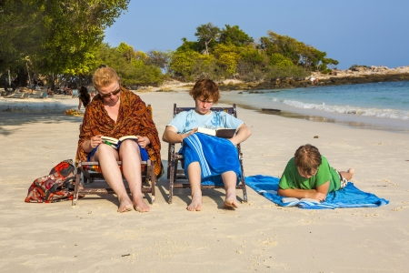 family is enjoying the sun and relaxing and reading books at the beautiful beach photo