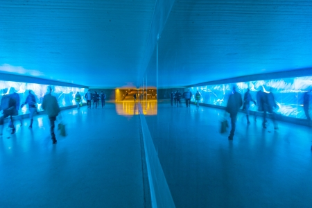 tunnel with pedestrians in motion in blue cool light photo