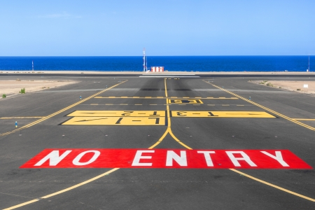 no entry sign: no entry sign at the runway of the airport with ocean in background