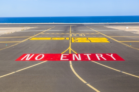 no entry sign at the runway of the airport with ocean in background photo