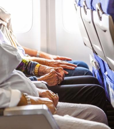 hand van een oudere dame zitten in het vliegtuig