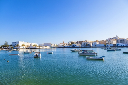remodelled: ARRECIFE , SPAIN - MAR 31: people anchor the boats in Charco de San Gines on MAR 31,2013 in Arrecife, Spain. The harbor area was remodelled by Canarian architect Caesar Manrique in 1984.