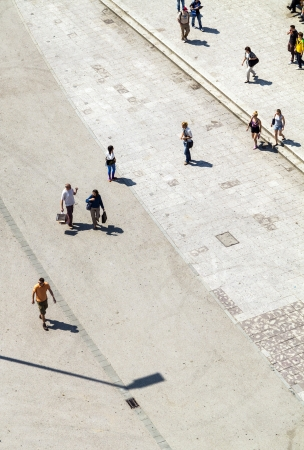 paveway: people walking at the street with long shadows Editorial