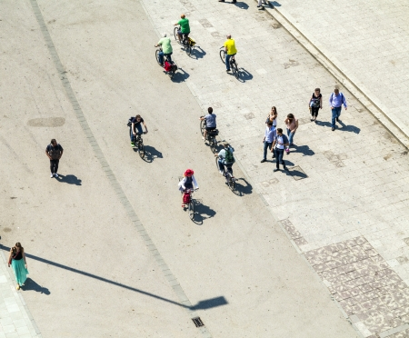 walking zone: people walking at the street with long shadows Editorial