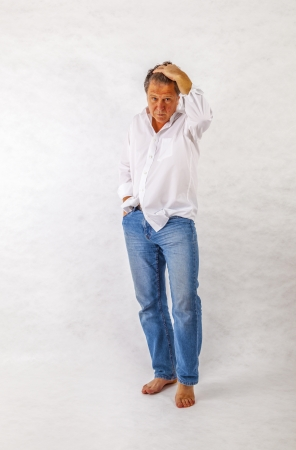 Mature man standing up against a white background photo